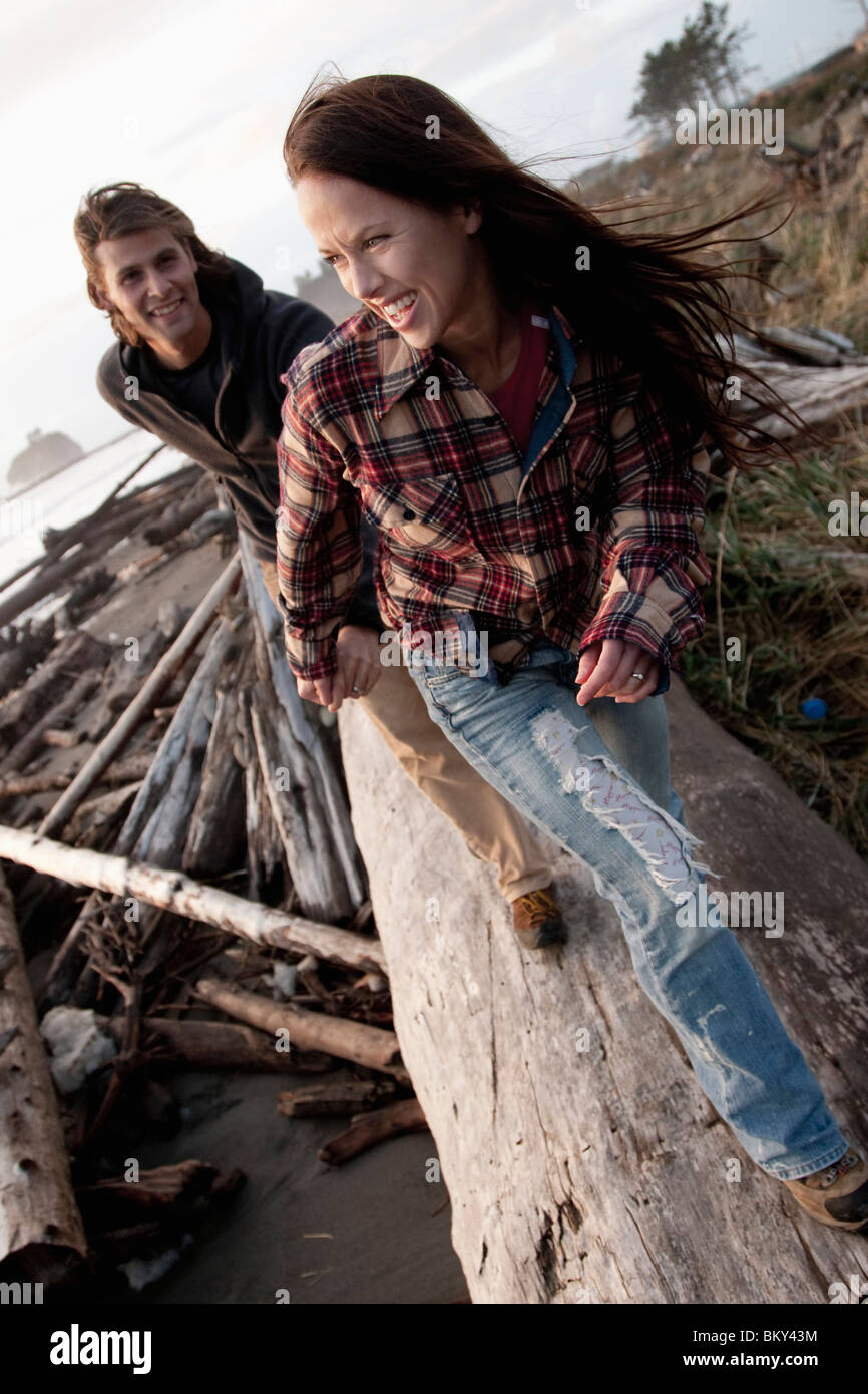 A young couple smile while walking along a beach log. - Stock Image