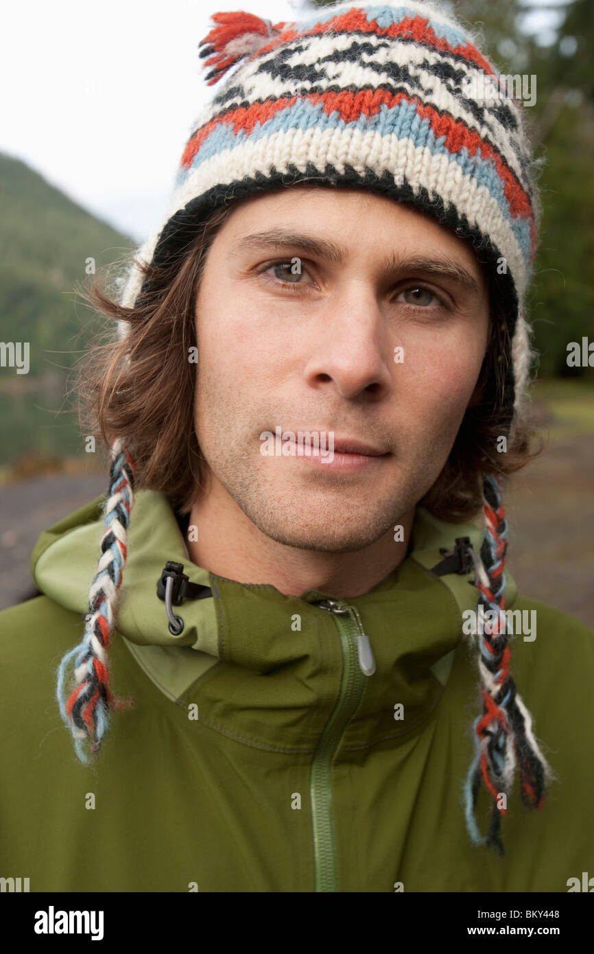 Portrait of a young man wearing a parka and winter hat. - Stock Image