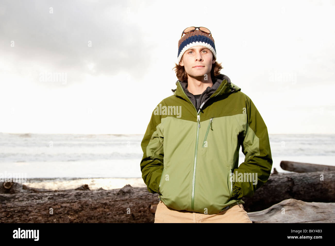 Portrait of young, outdoorsy man in jacket and hat while hiking at La Push Beach, Washington. - Stock Image