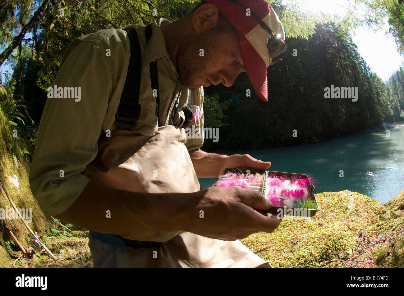 A man picks a fly from his fly box while  fishing in Squamish, British Columbia. - Stock Image