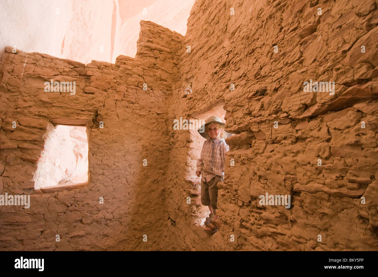 A young boy explores an Anasazi Ruin on the San Juan River, Mexican Hat, Utah. - Stock Image