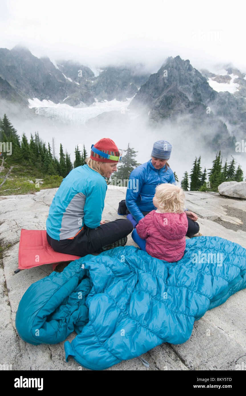 Two women and a girl playing a game at a campsite, Mount Baker Wilderness, Bellingham, Washington. - Stock Image