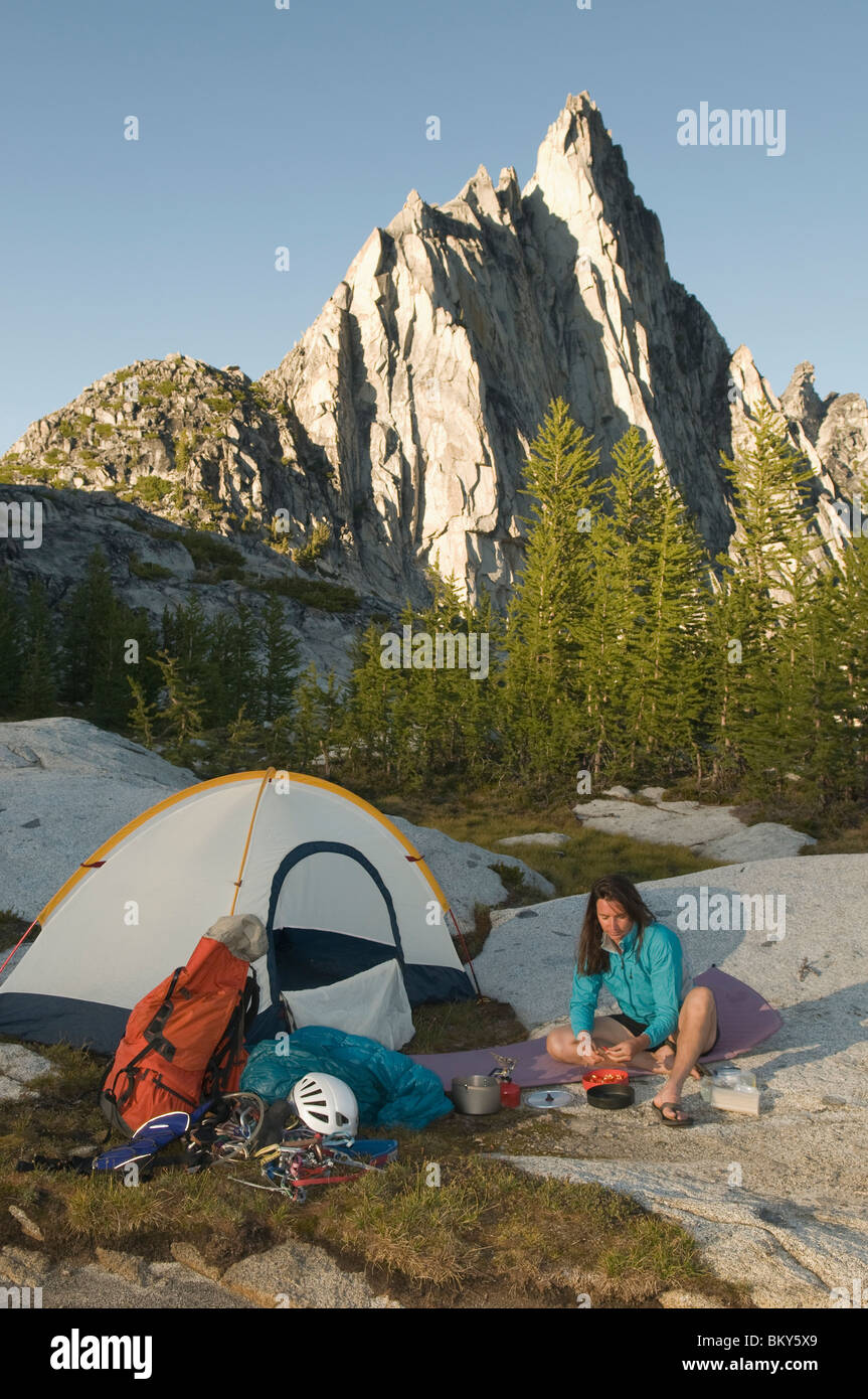 A woman camping below Prussik Peak, Enchantment Peaks, Alpine Lakes Wilderness, Leavenworth, Washington. - Stock Image