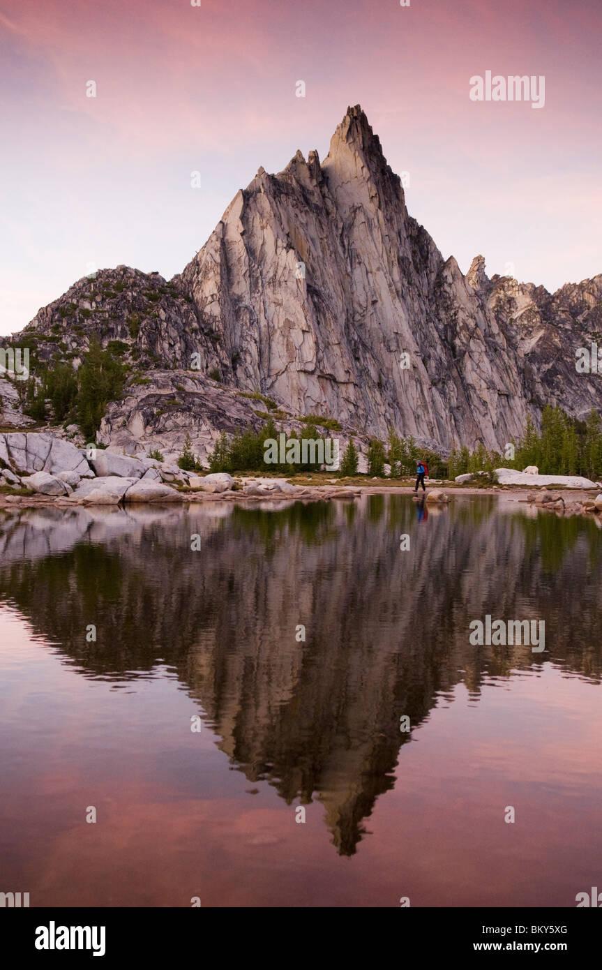 A woman hiking at sunset near mountain goats on a lake below Prussik Peak, Alpine Lakes Wilderness, Leavenworth, - Stock Image