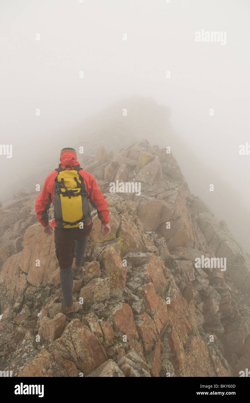 A man climbing up the Northeast Ridge of Grizzly Peak in the fog and snow, San Juan National Forest, Durango, Colorado. - Stock Image