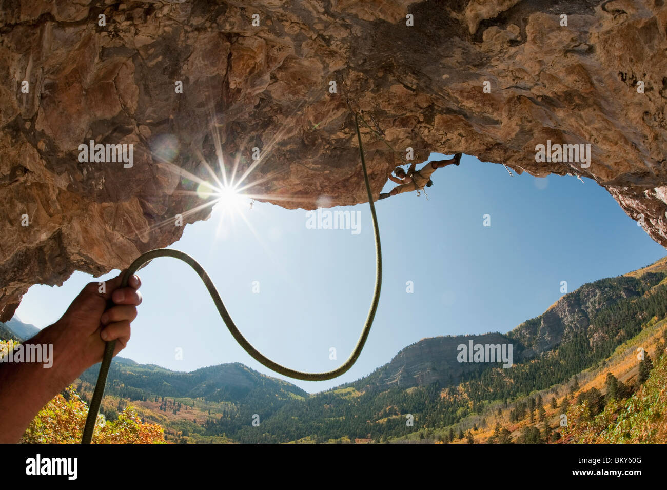 A belayers hand holding rope leading to a man rock climbing at the Golf Wall, San Juan National Forest, Durango, - Stock Image