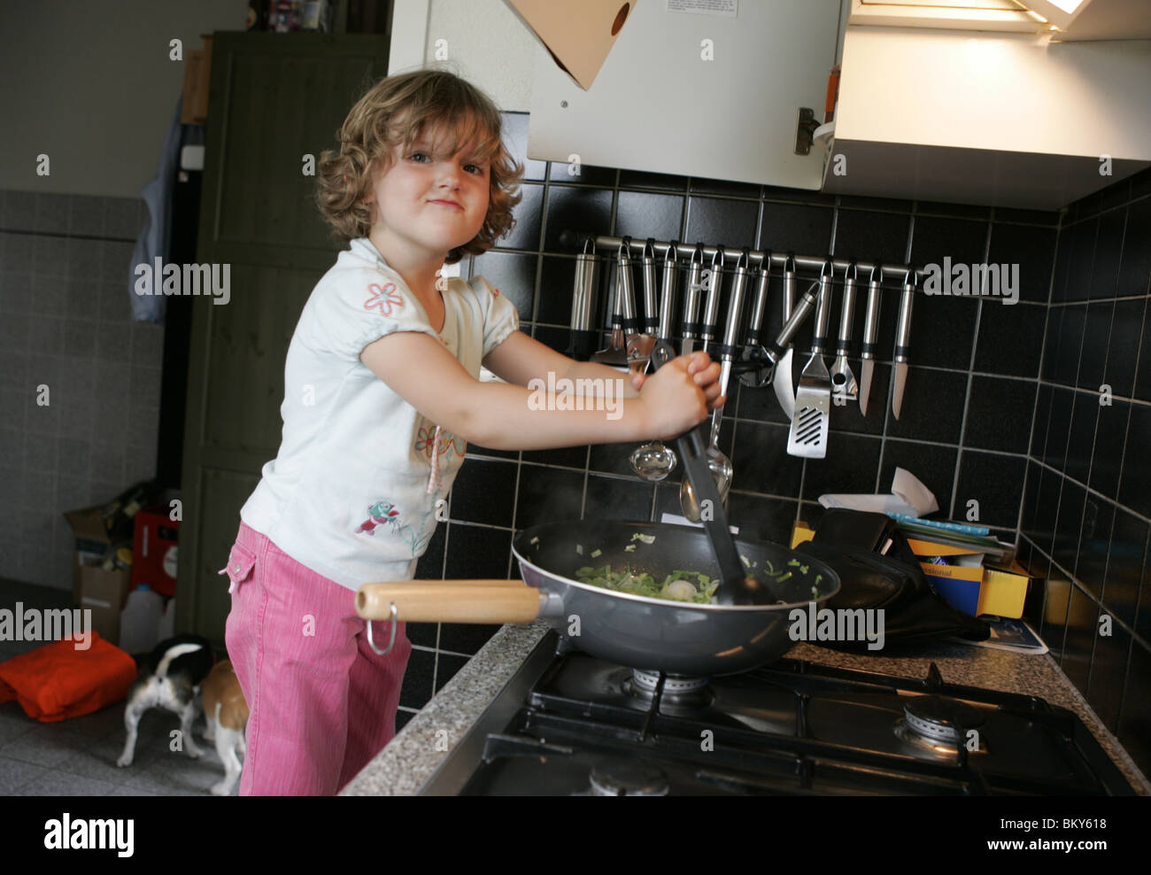 Child in kitchen cooking - Stock Image