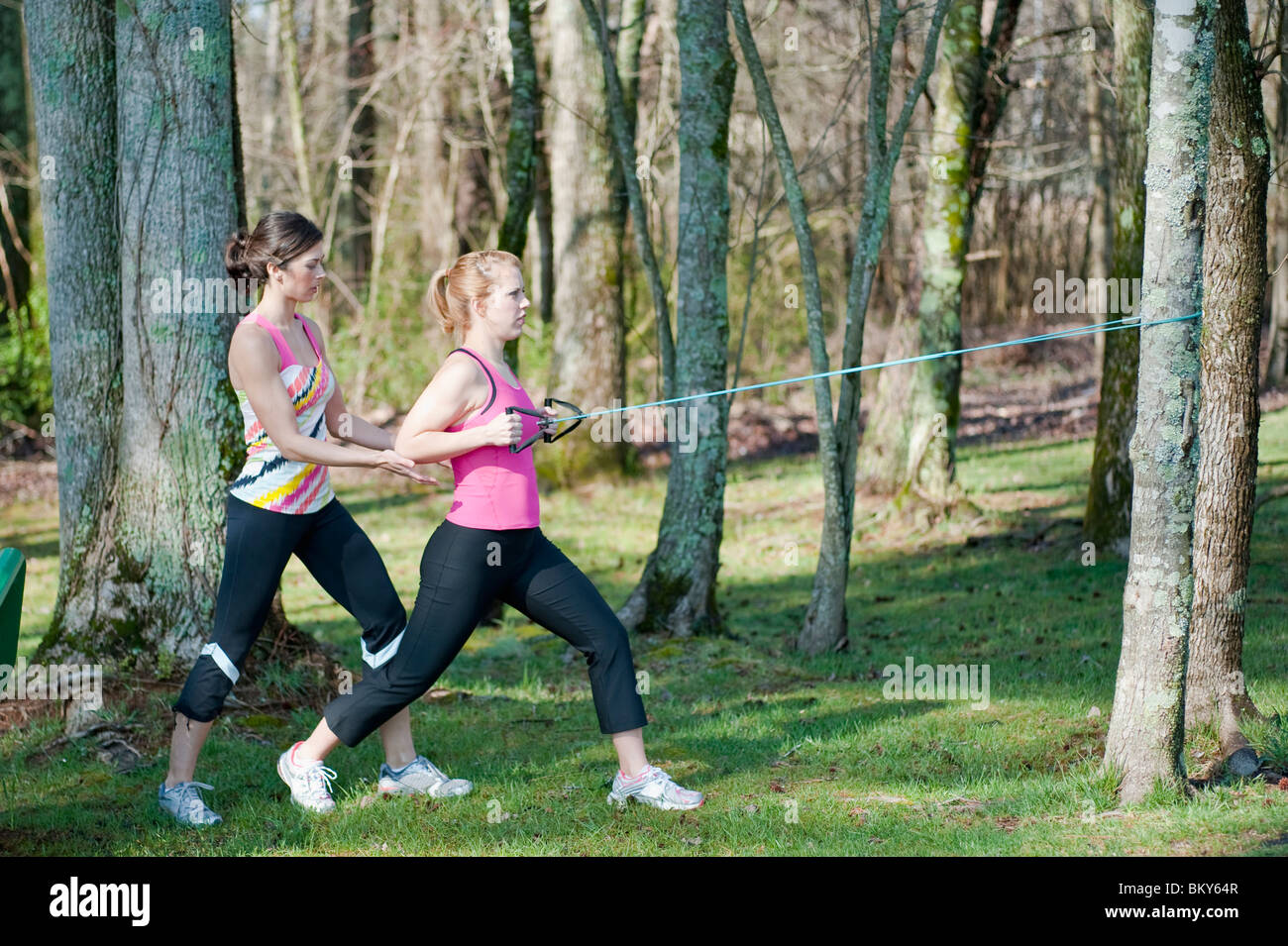 Two women in their mid-20's working out  outdoors. - Stock Image