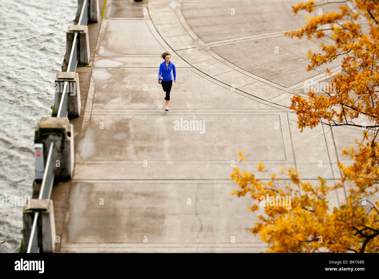 An athletic female in a blue jacket jogging along the Portland, Oregon waterfront. - Stock Image