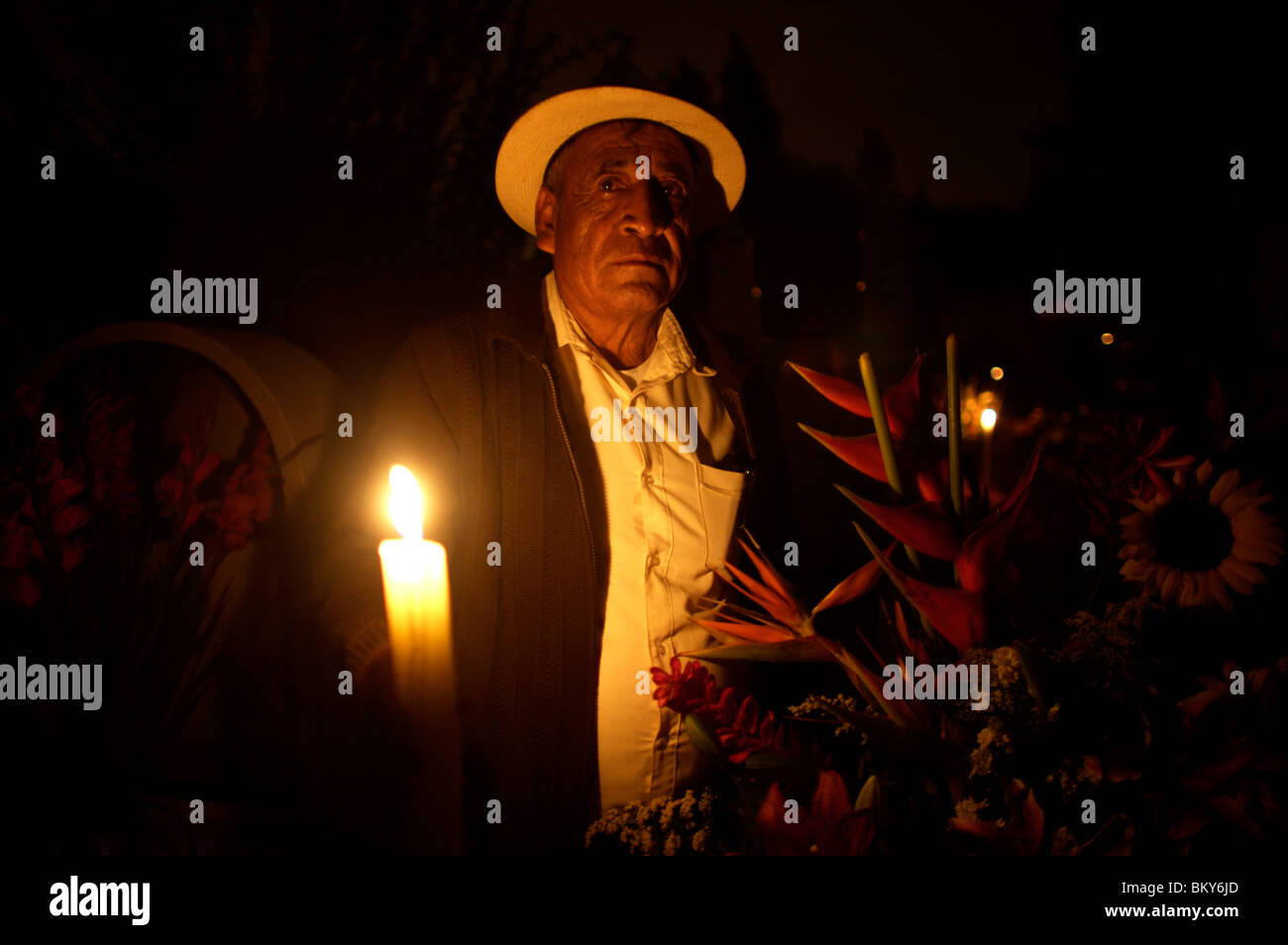 A man holds a candle as he posses by the grave of a family member in San Gregorio Atlapulco on the outskirts of - Stock Image