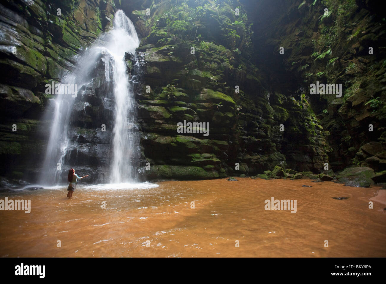 A woman observes a waterfall in Brazil. - Stock Image