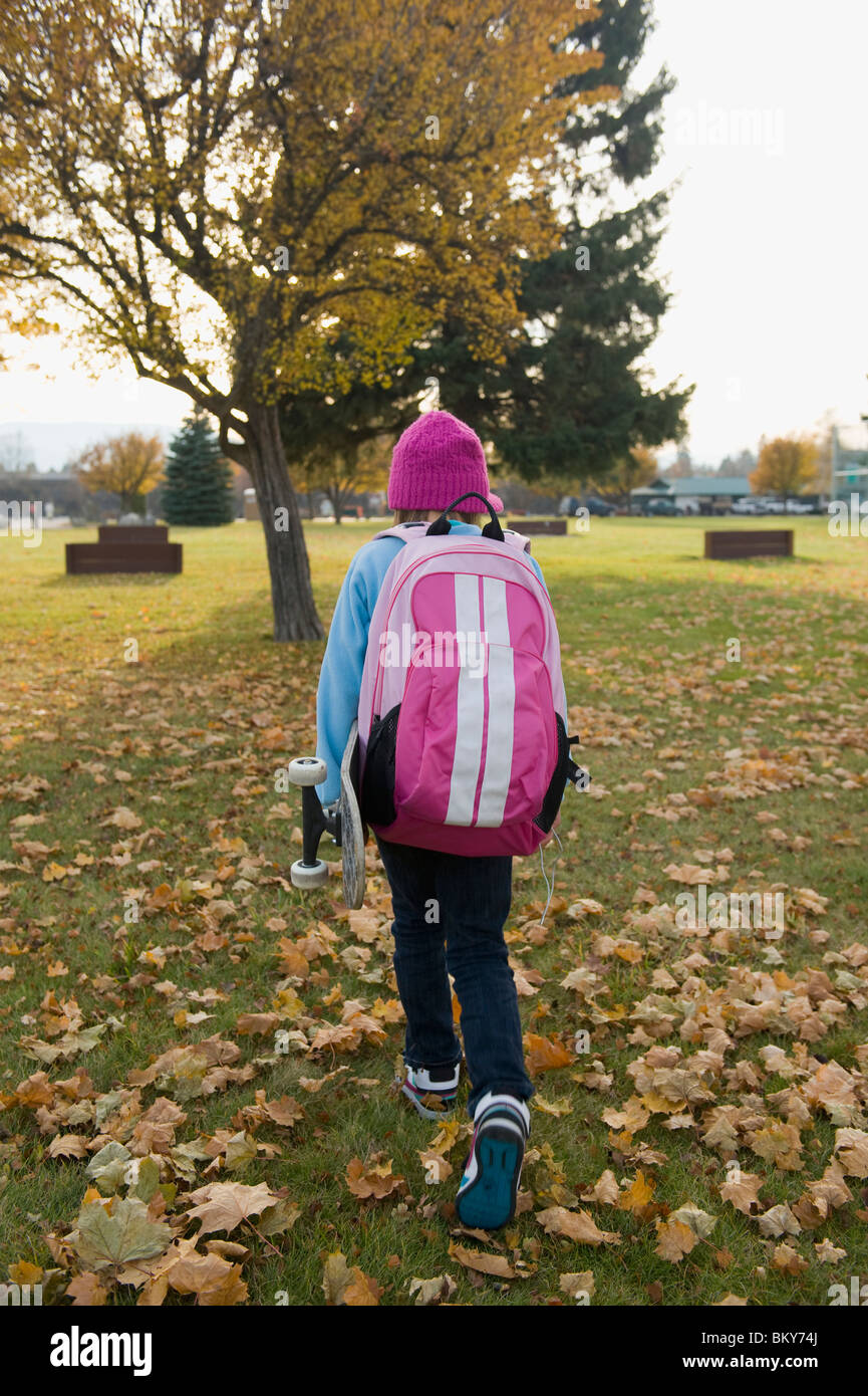 A young girl, carrying her skateboard, walks home from school on a fall day. - Stock Image