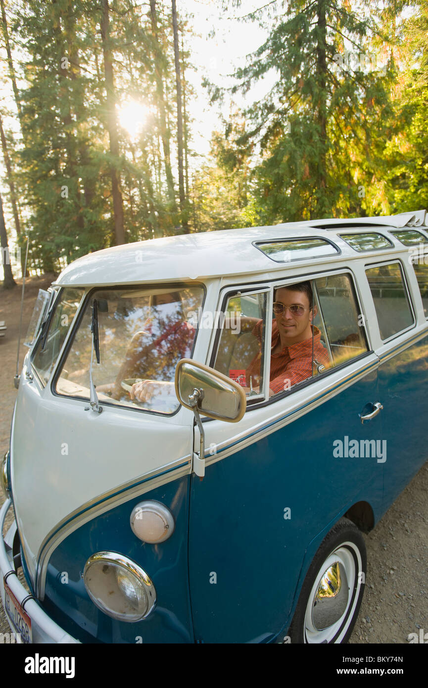 A young man and woman pose for a picture from inside their vintage van. - Stock Image