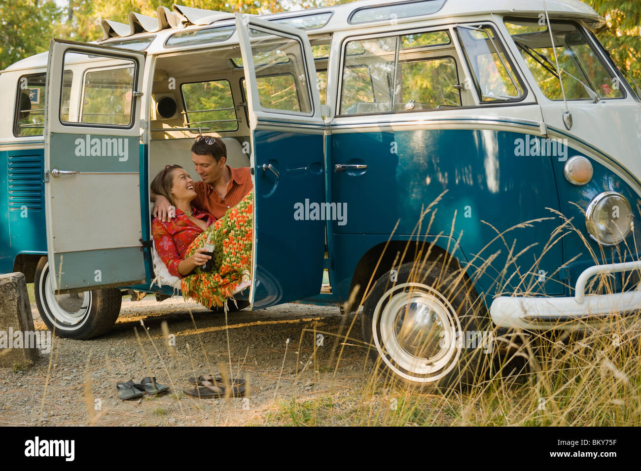 A young couple relax inside a classic van. - Stock Image