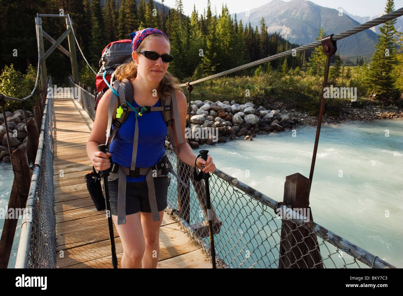 A female backpacker in her early thirties crosses a suspension bridge over the Vermillion River while hiking the - Stock Image