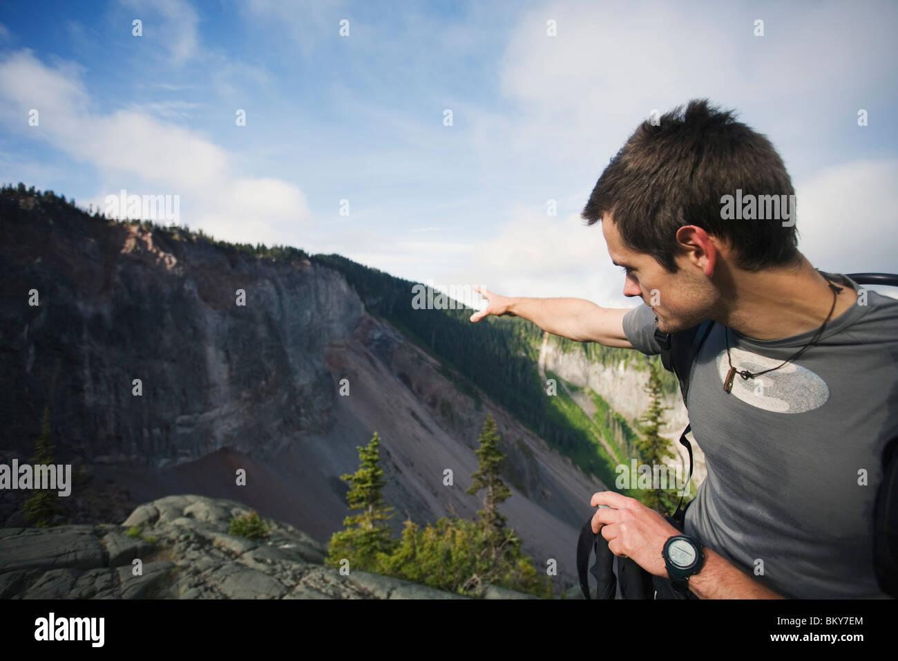 A man explains the landslide hazard potential from The Barrier, an unstable volcanic cliff near Squamish, British - Stock Image