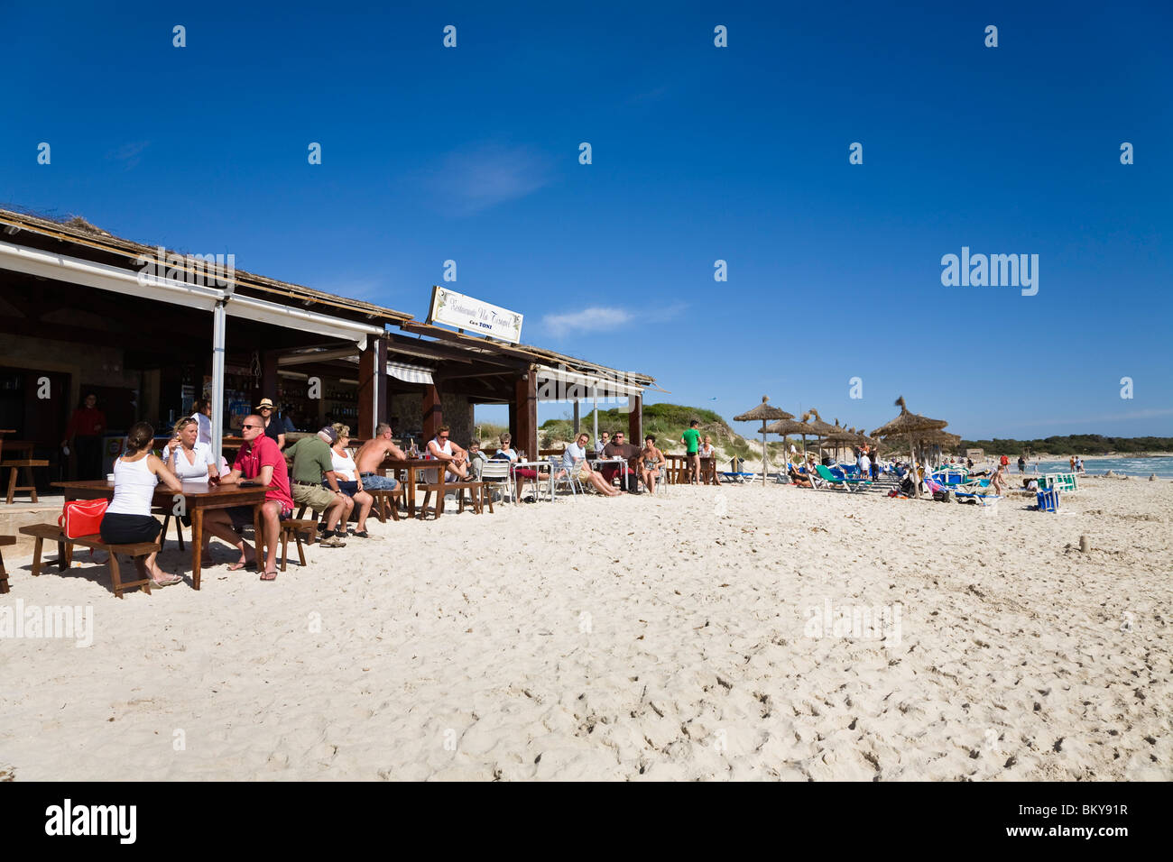 People sitting in a beach bar at the beach of Es Trenc, Mallorca, Balearic Islands, Spain, Europe - Stock Image