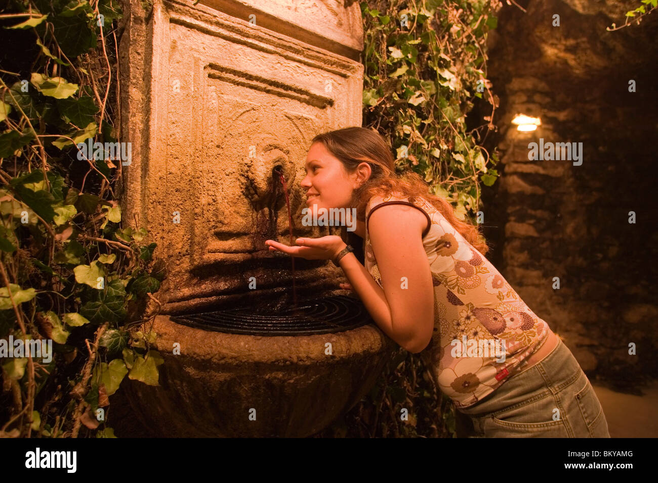 Woman at wine fountain in Buda Castle Labyrinth, Woman tasting red wine of the wine fountain in Buda Castle Labyrinth, Stock Photo