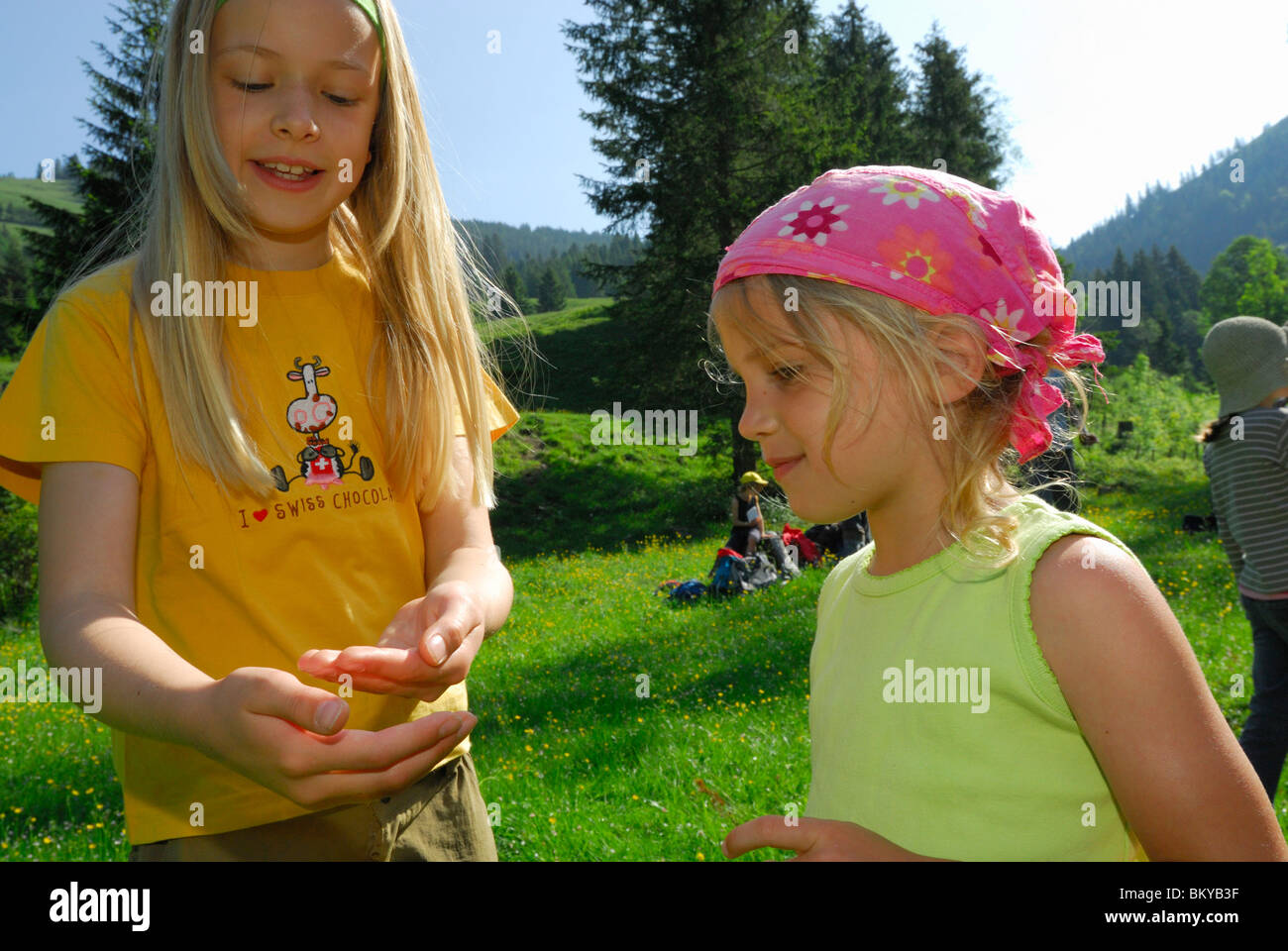 Two girls looking at something in a hand, Bavarian Alps, Upper Bavaria, Bavaria, Germany - Stock Image