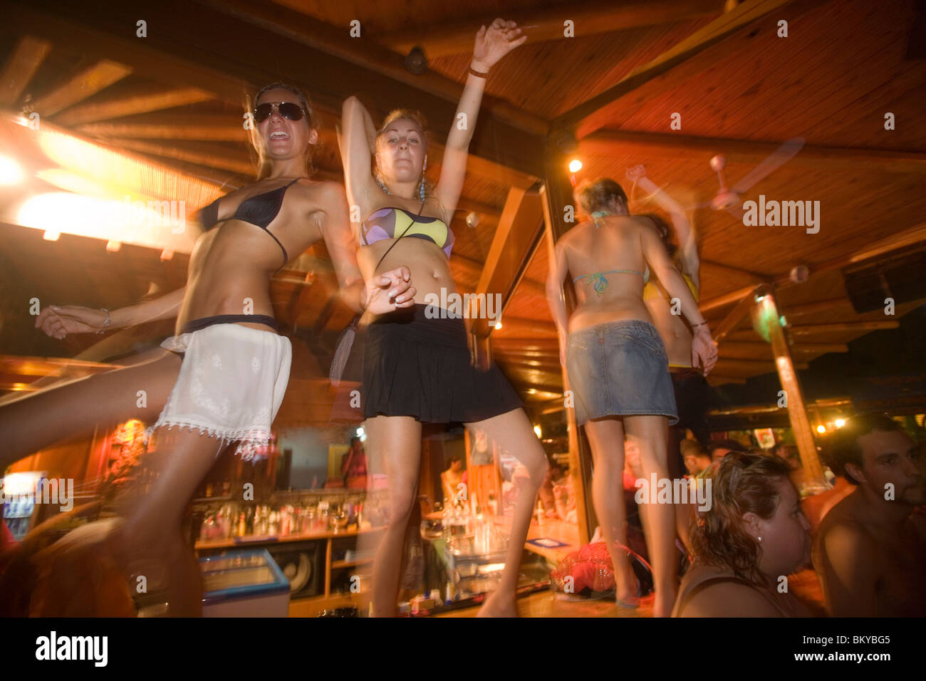 Young girls dancing a table during the full moon party, Tropicana Club, Paradise Beach, Mykonos, Greece - Stock Image