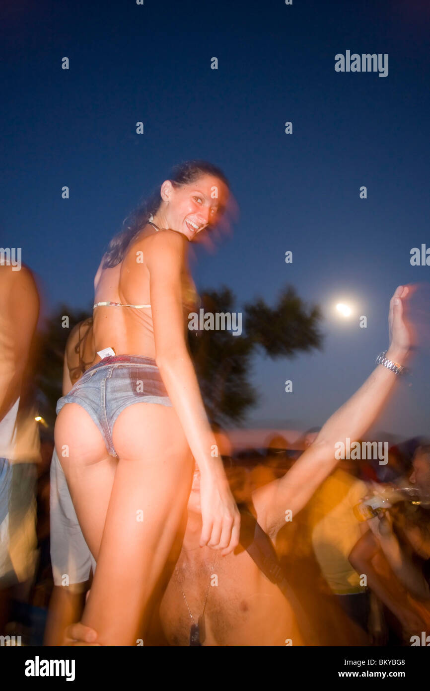 Young girl dancing by the full moon party of the Tropicana Club, Paradise Beach, Mykonos, Greece - Stock Image