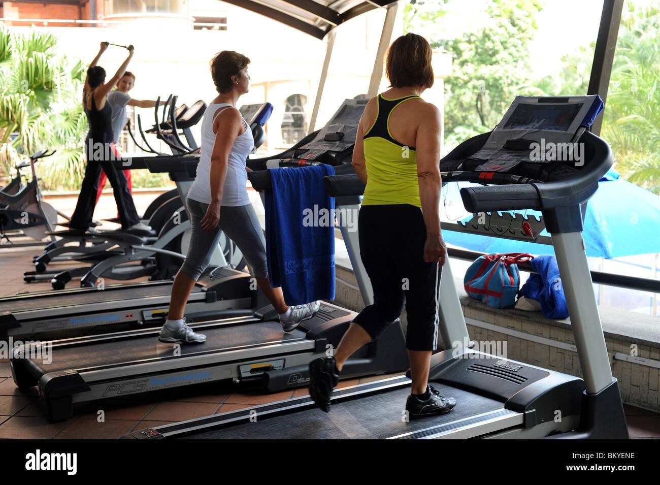4 women walking on treadmills in Medellin gym. - Stock Image