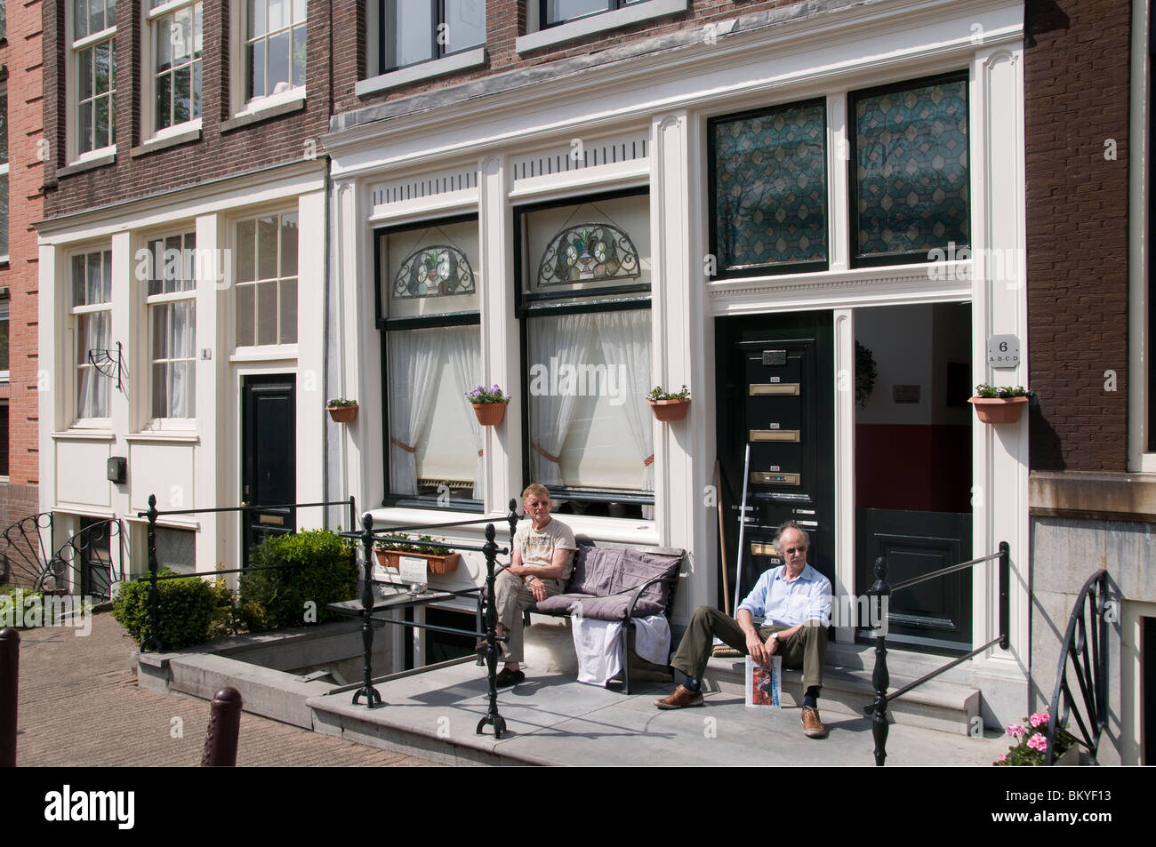 Amsterdam Holland Jordaan  Prinsengracht canal house two old men in the sun - Stock Image