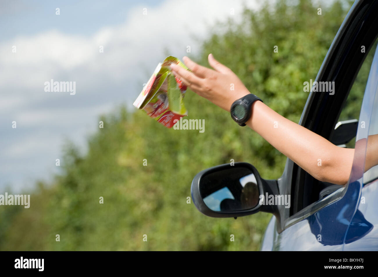 Somebody throwing litter out of a car window. - Stock Image