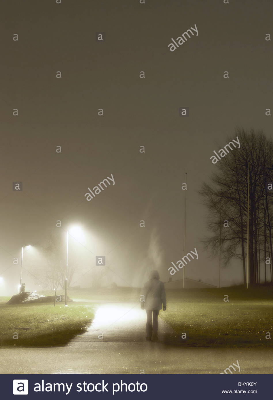 Woman walking in a housing area att night in mist, Sweden, 2008 - Stock Image