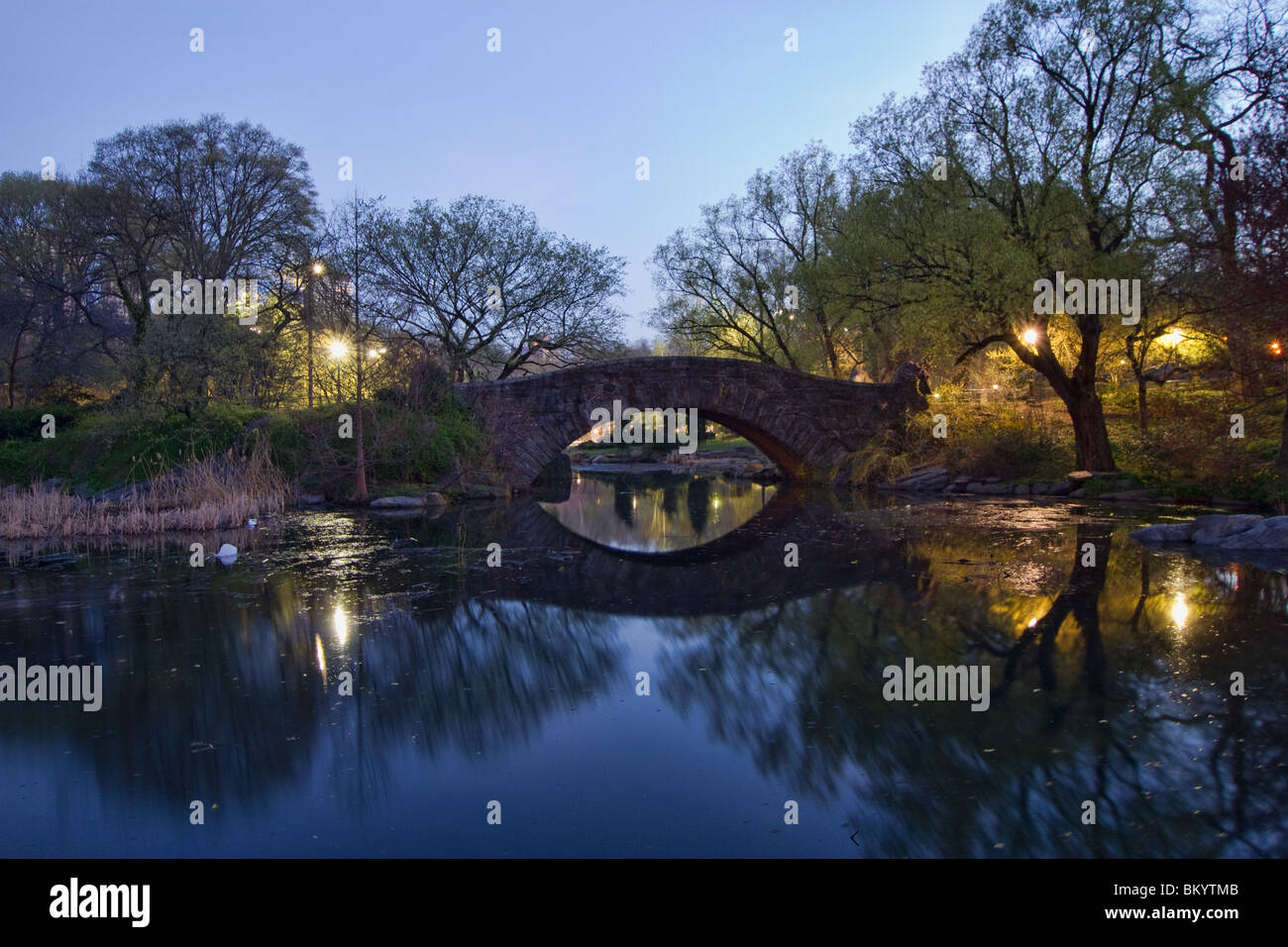 Look north across the Pond in Central Park at Gapstow Bridge at dawn. - Stock Image
