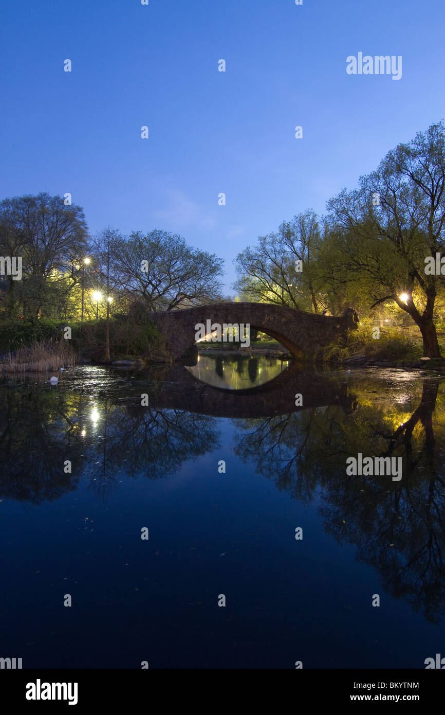 Looking north across the Pond in Central Park at Gapstow Bridge at night. - Stock Image