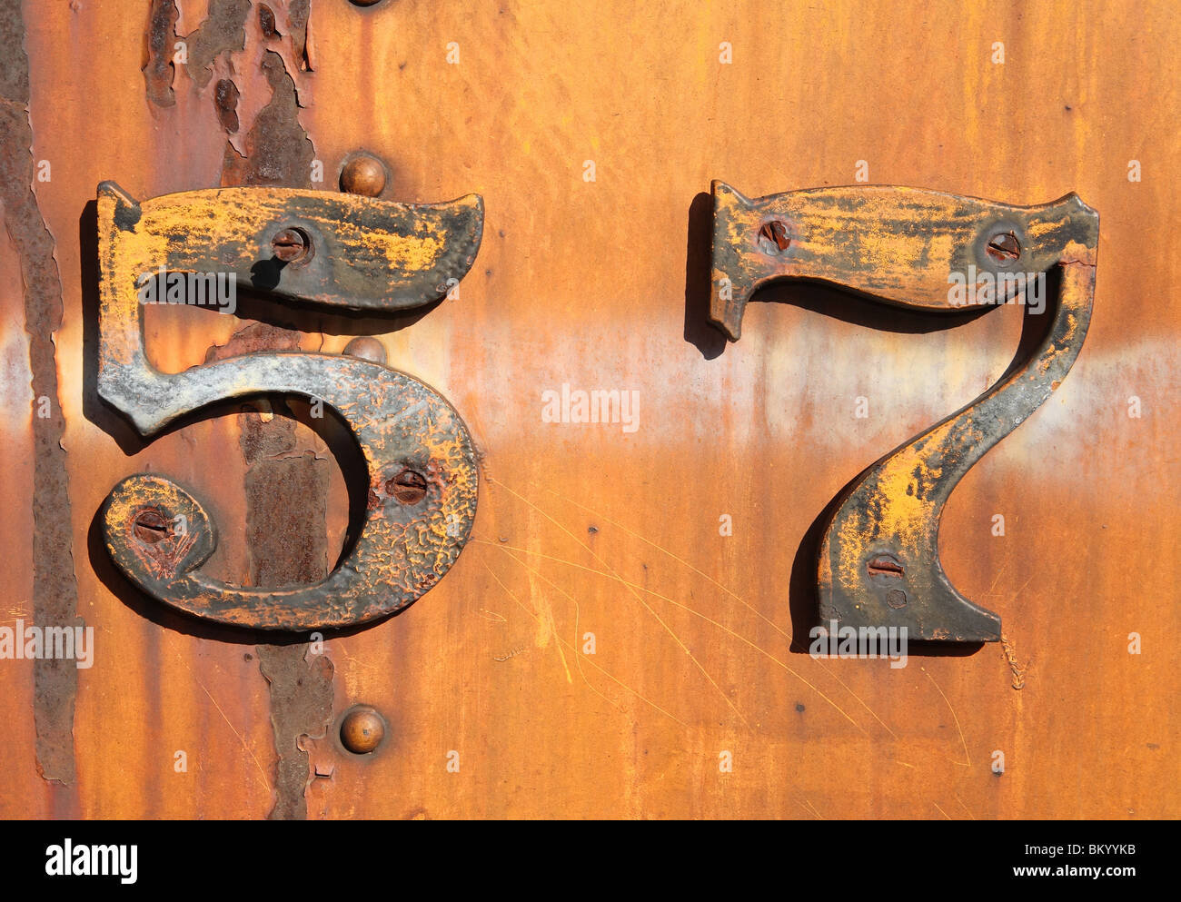 grungy rusty number five and seven 57 on old yellow metal train - Stock Image