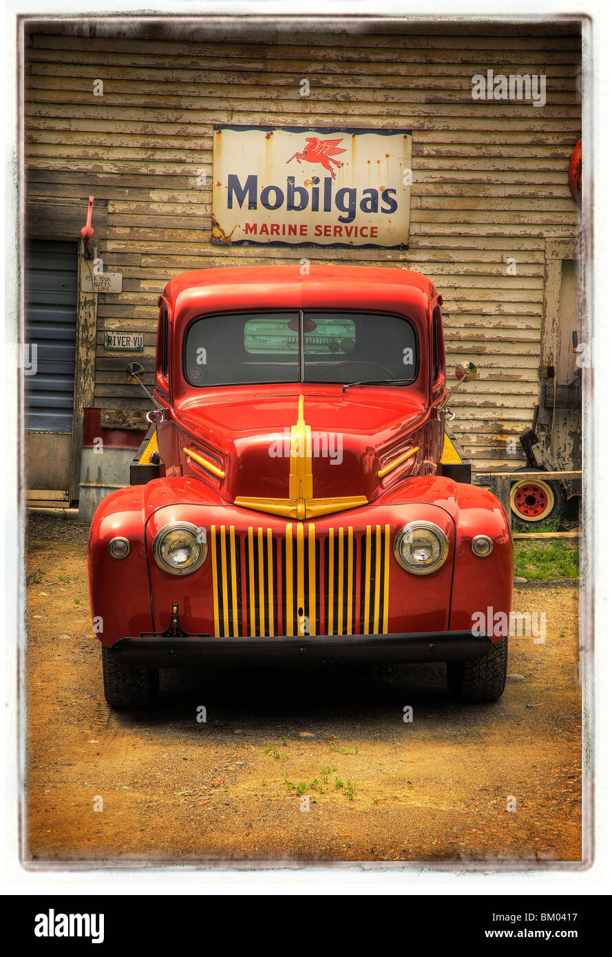 Classic old red truck parked in front of a Mobilgas sign. - Stock Image