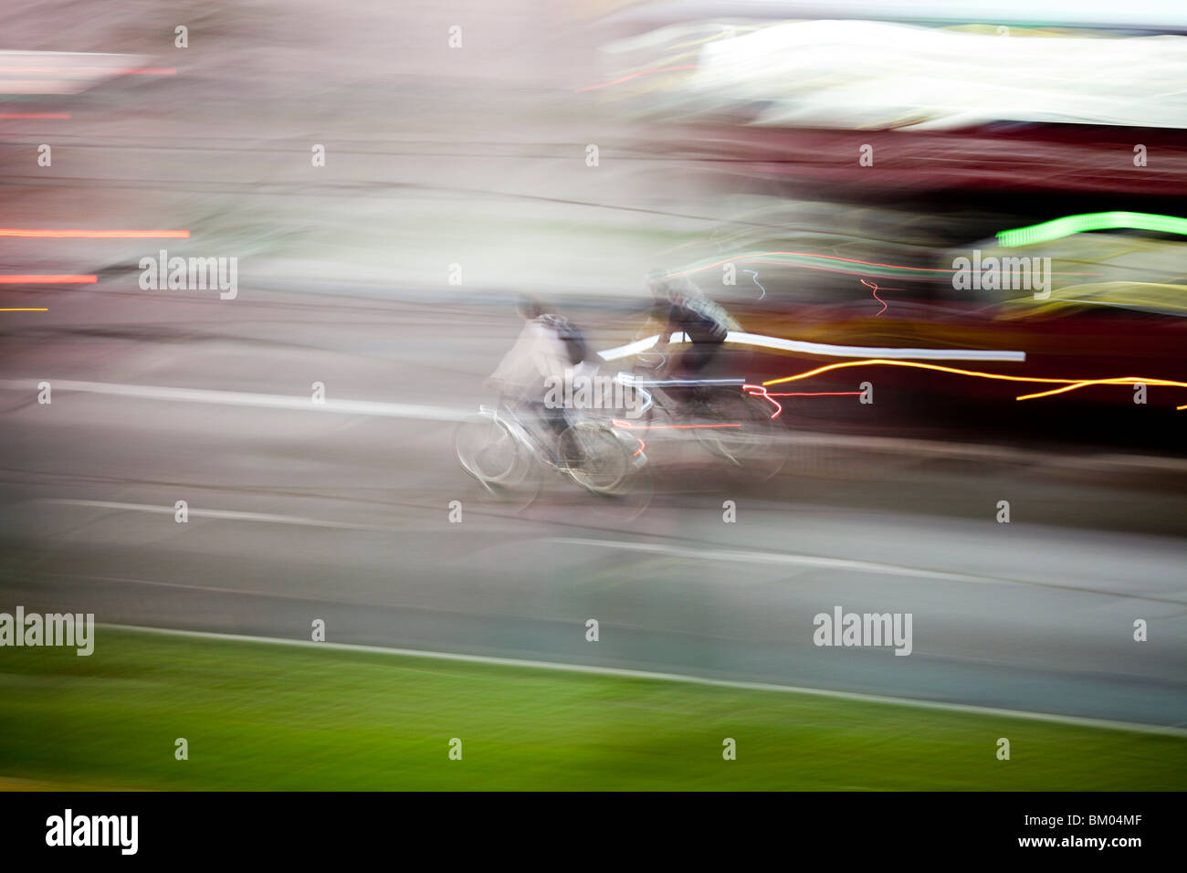 Panning shot of cyclists by night, Berlin, Germany - Stock Image