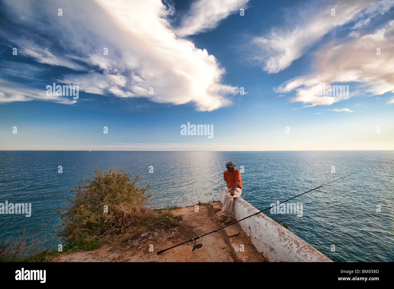 Fisherman on the top of a cliff, town of Porches, municipality of Lagoa, district of Faro, region of Algarve, Portugal - Stock Image