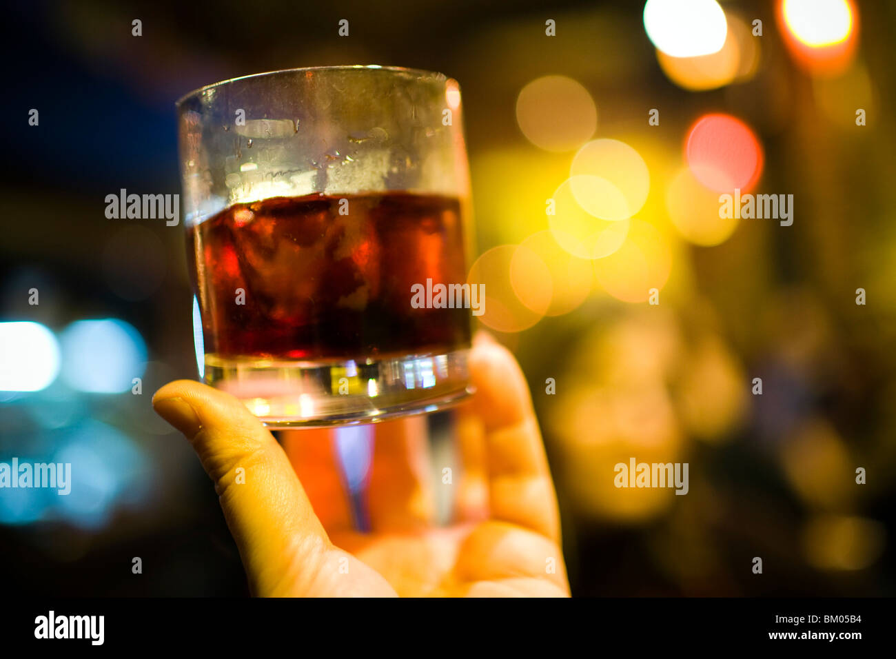 Hand holding a glass with alcoholic beverage, Seville, Spain - Stock Image