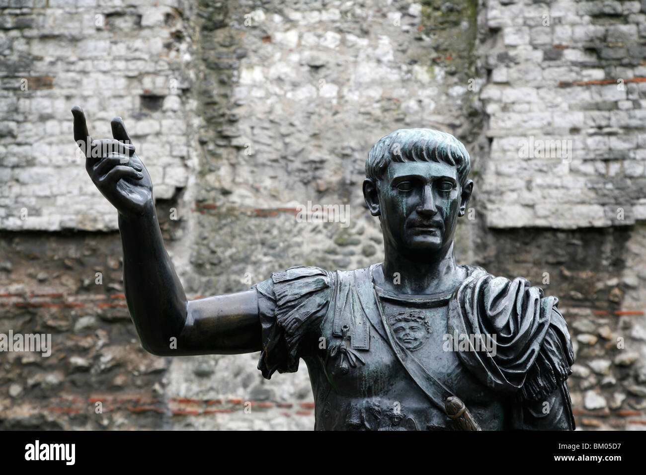 Statue of Emperor Trajan in front of remains of the old London Wall at Tower Hill, City of London, UK - Stock Image