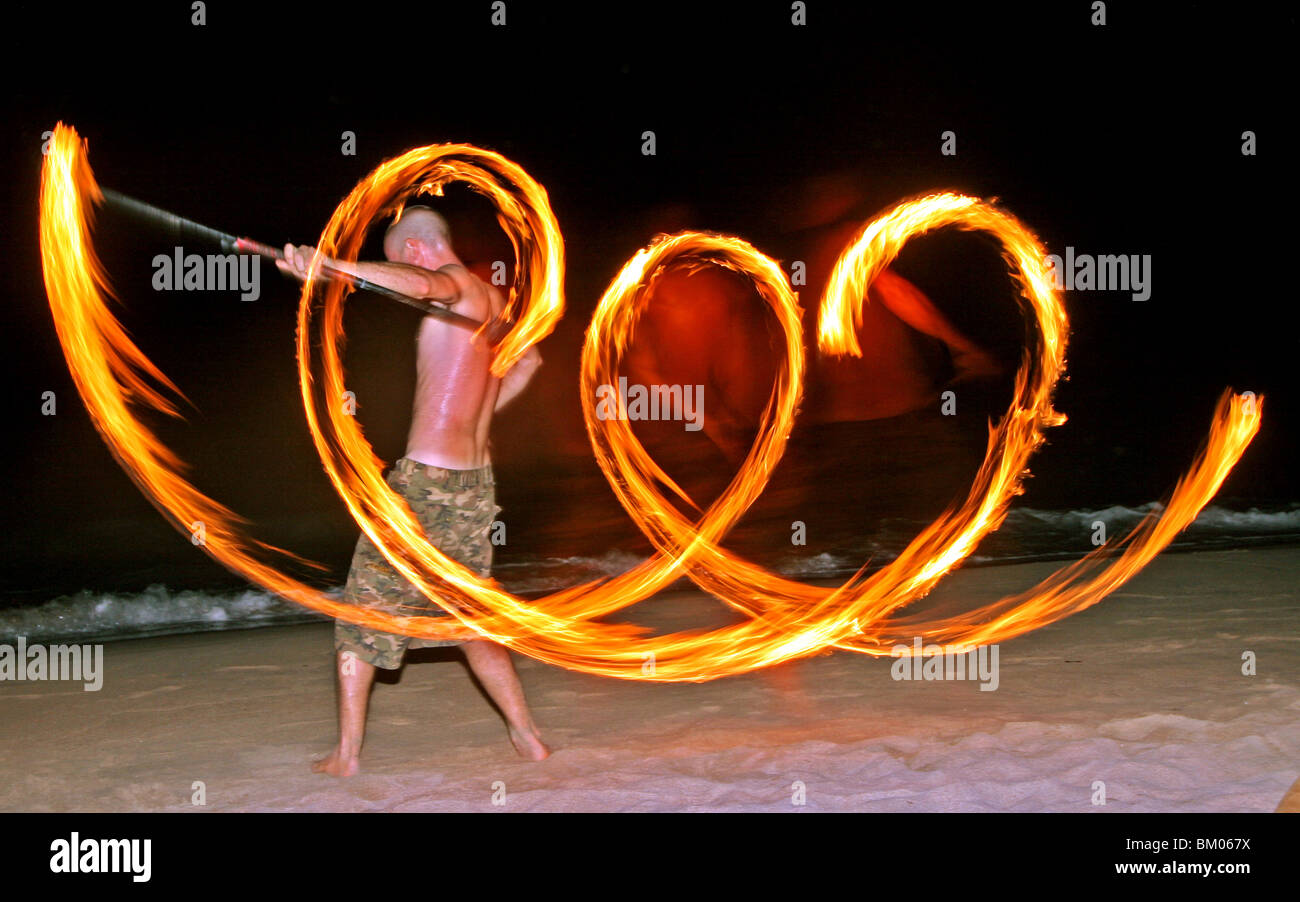 A Fireshow Artist rotates fire on chains in this long exposure image giving the impression of a man engulfed in - Stock Image