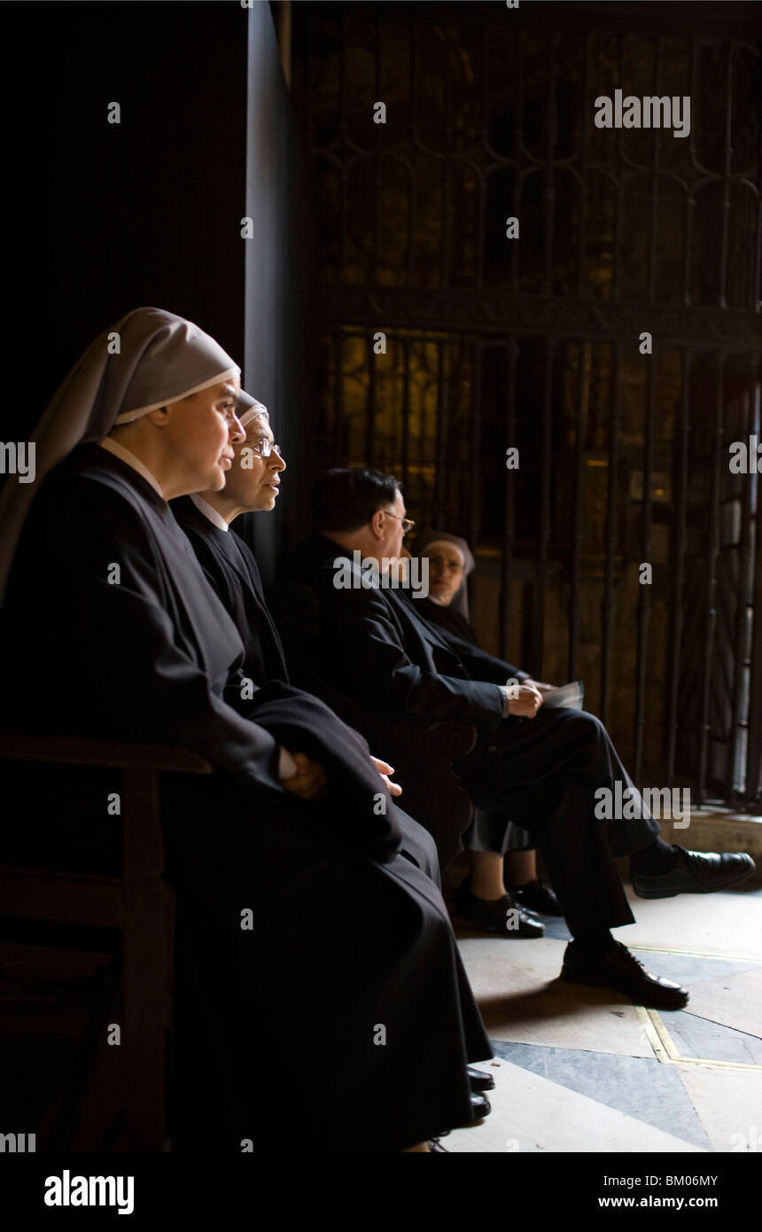 Clergy persons inside Seville's cathedral, Spain - Stock Image