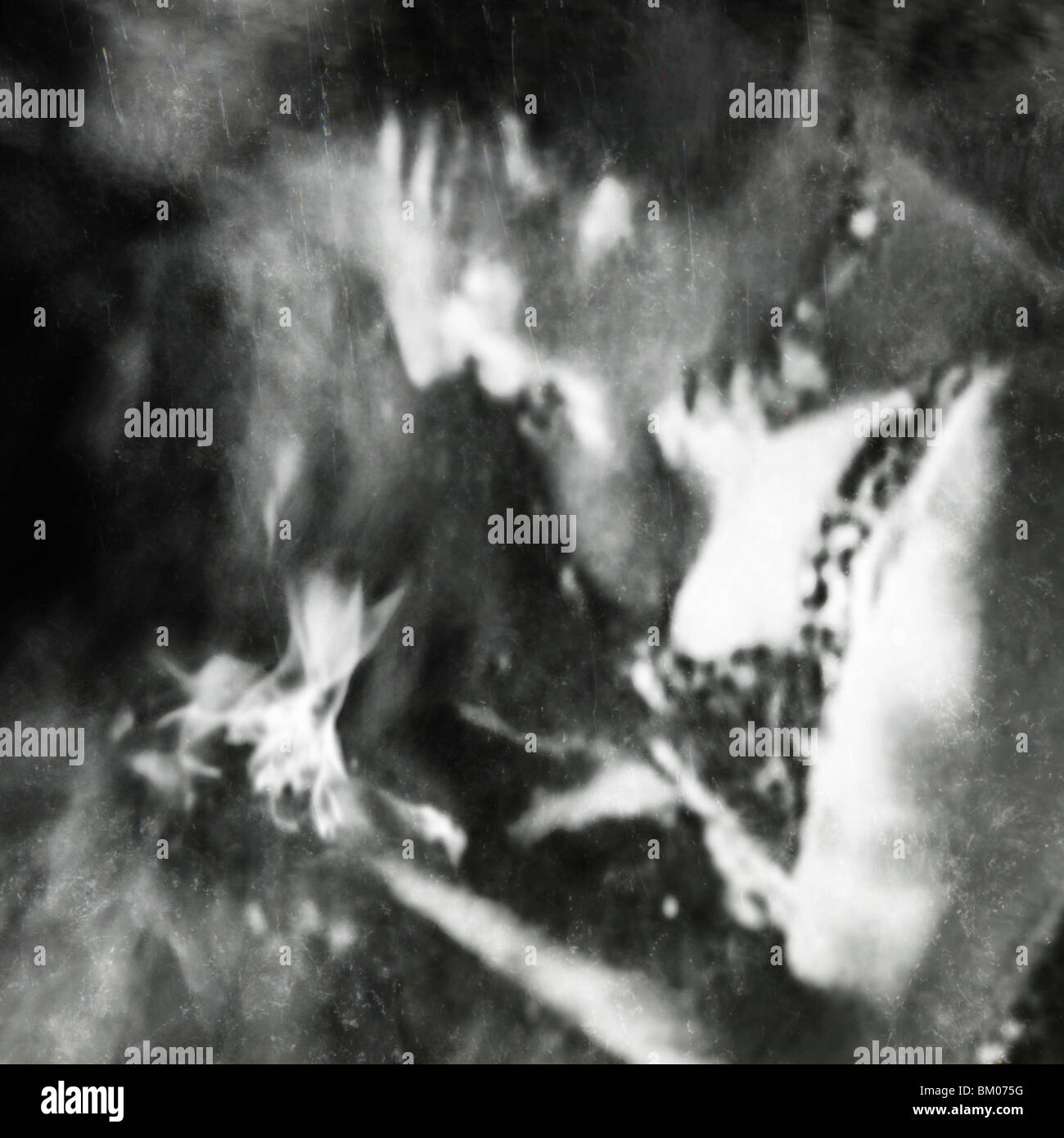 a woman gazes down into the flames in her hands - Stock Image