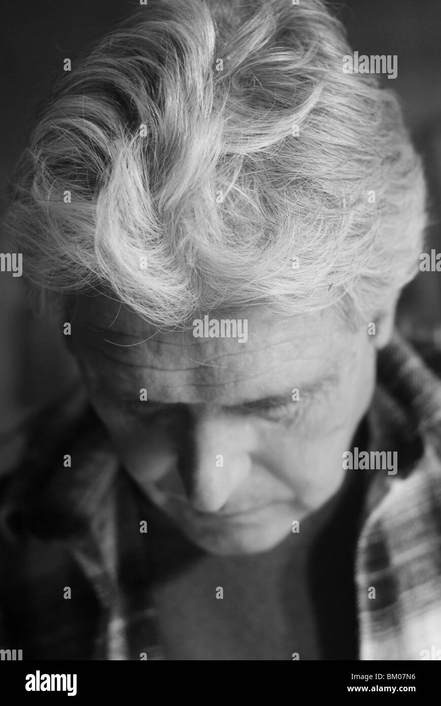a pensive senior man concentrates while working, a portrait in black and white, suburban albuquerque, new mexico, - Stock Image