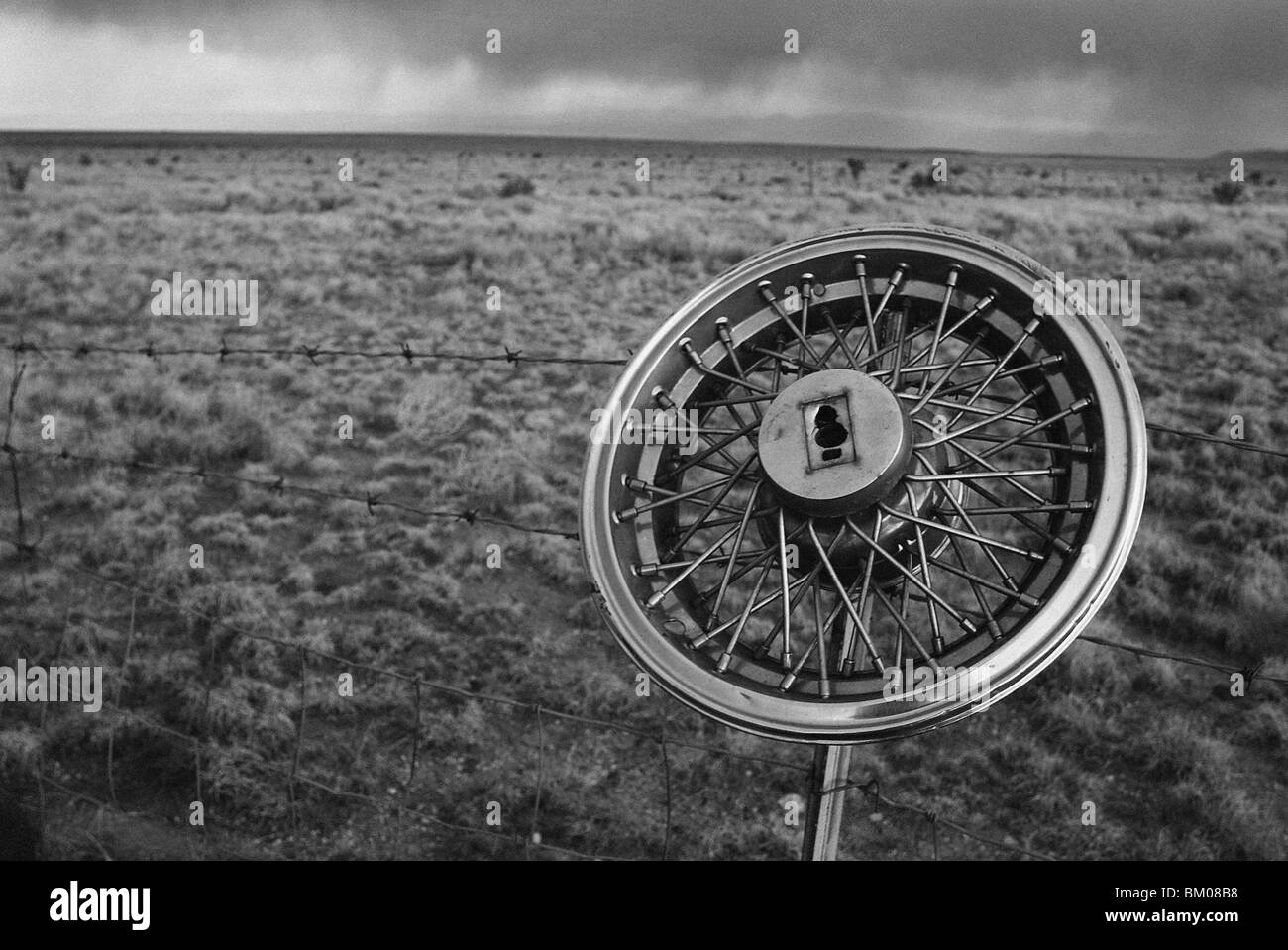 a hubcap on a barbed wire fence with the southwest desert landscape, santa fe, new mexico - Stock Image
