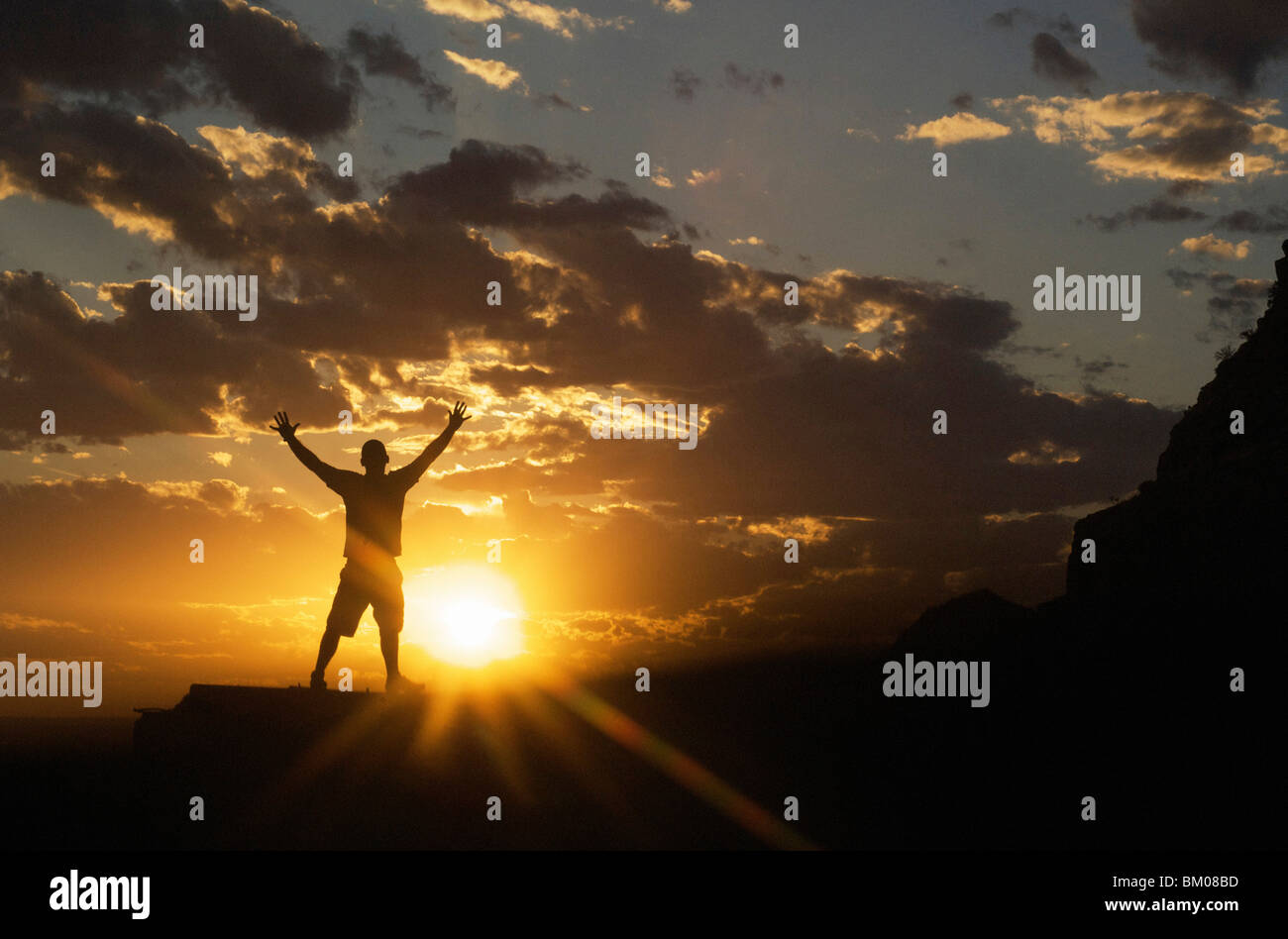 nature scenery and inspirational concepts: silhouette of man celebrating the dramatic sunset sky standing arms spread - Stock Image