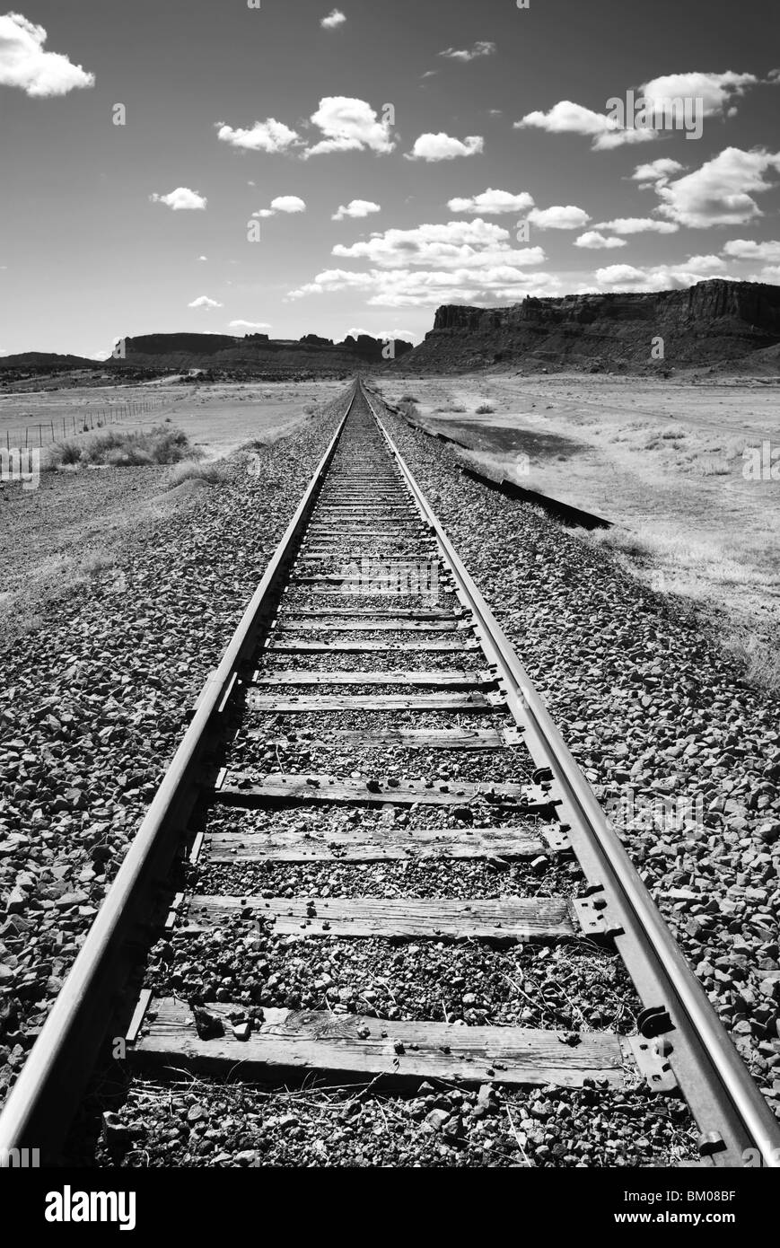 train tracks disappearing into the desert landscape, moab, southeastern utah, contrast the vast desert landscape - Stock Image