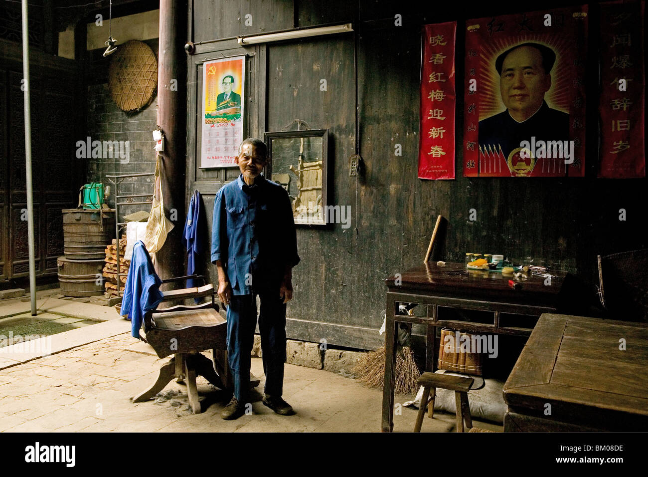 village barber, Mao portrait, courtyard of timber house in Chengkun, ancient village, living museum, China, Asia, - Stock Image