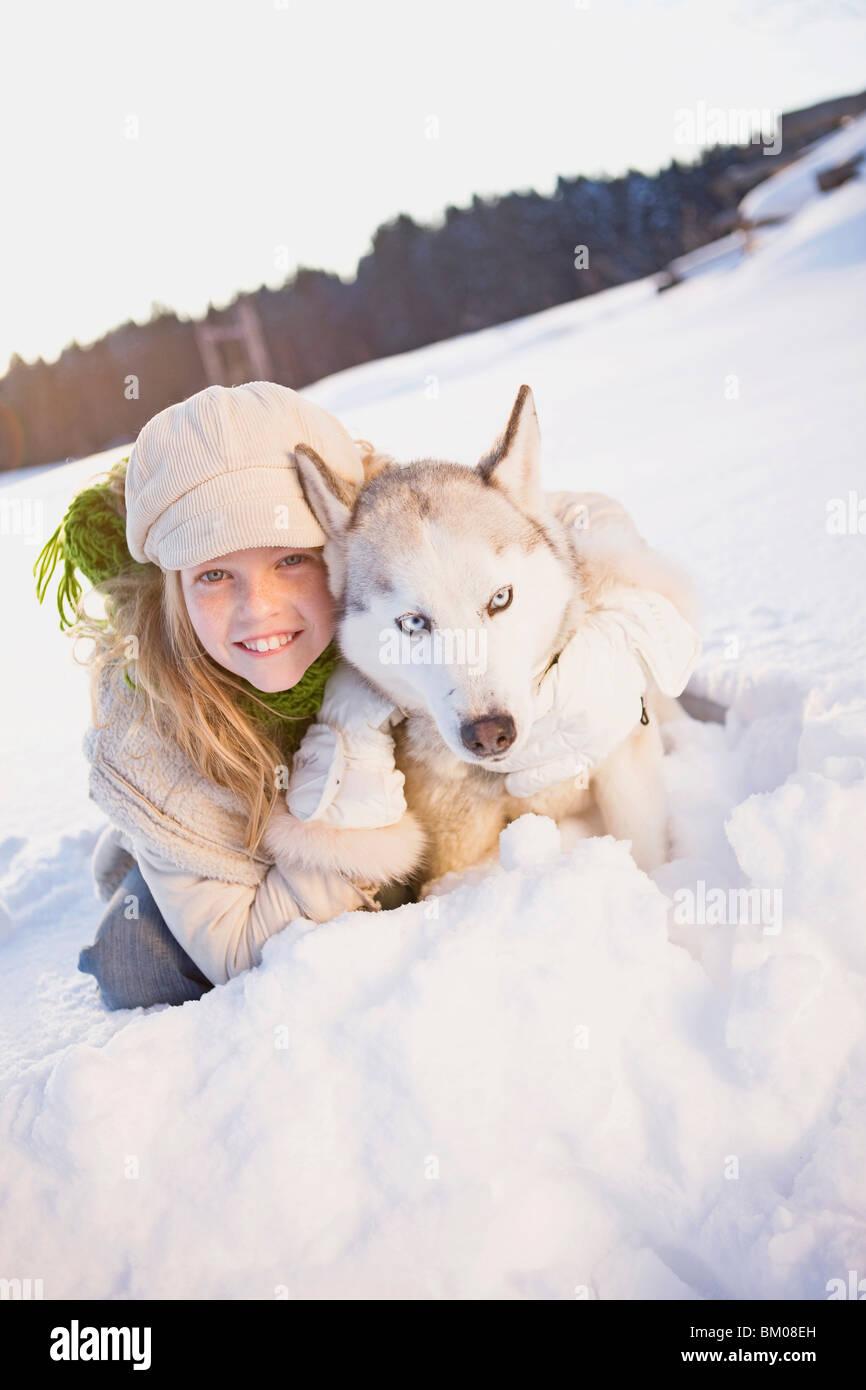 Girl embracing siberian husky - Stock Image