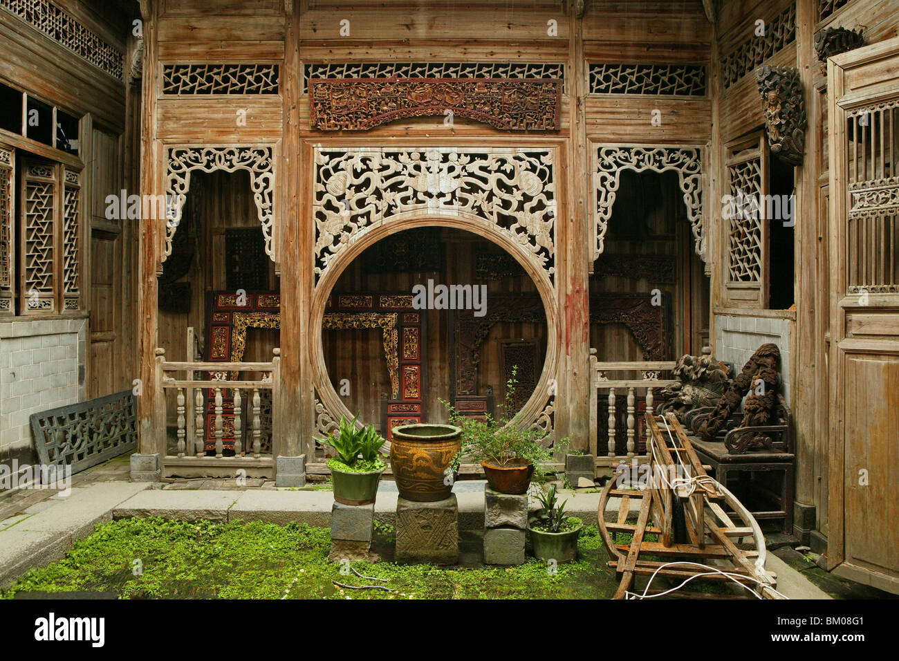 courtyard with elaborate carved timber screens, pot plants, Hongcun, ancient village, living museum, China, Asia, - Stock Image