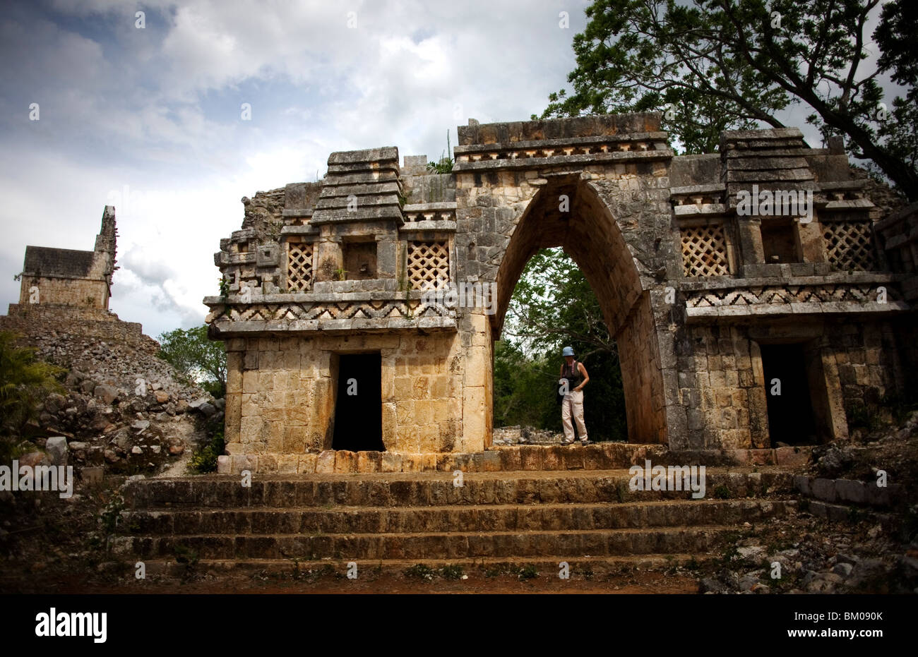 """A tourist walks by a Mayan arch among the ruins of Labna, along the """"Puuc route,"""" in Yucatan state on Mexico's Yucatan Stock Photo"""