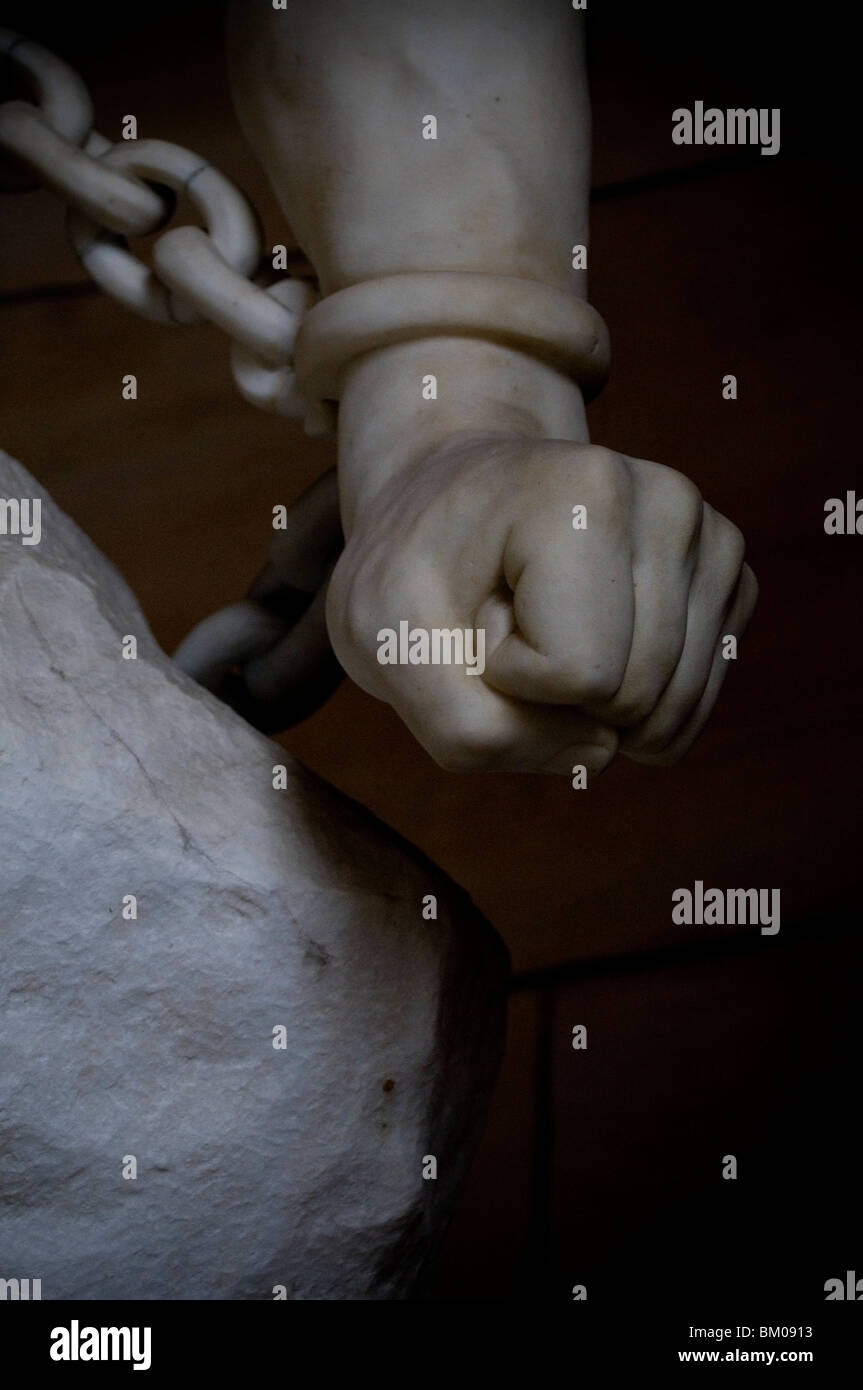 A close up of a statues clenched fist held with a chain - Stock Image