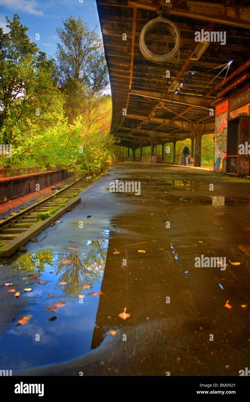 An old S-Bahn station unused since the 80s near Berlin with reflections in water - Stock Image